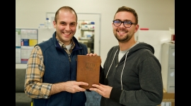 Alex Lorestani (left) and Nick Ouzounov (right) hold a copy of Paul Shapiro's book Clean Meat bound in leather that they produced in the lab. Credit: Eric Day